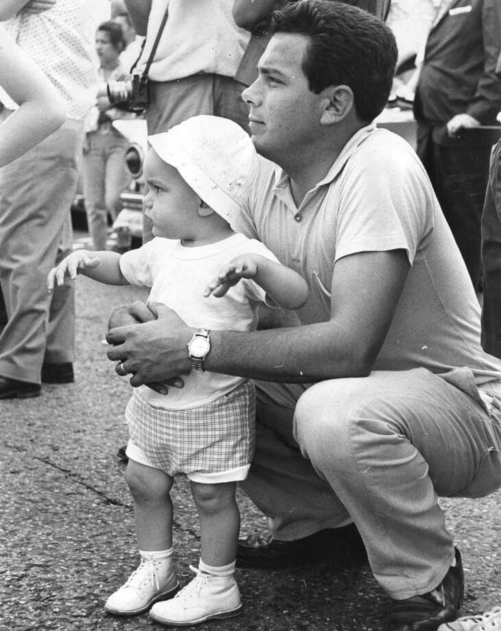 Parade are just the thing for small boys, and Gary Miques tells his father all about it. Gary's father, Antonio Miques, 6204 Grand Blvd., Houston, makes an attentive listener. Published April 30, 1962.