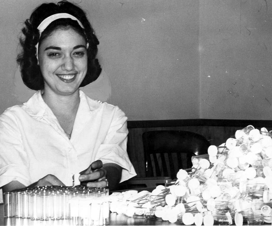 "04/25/1963 - Miss Rosalie Runfola is preparing some of the ""treasure capsules"" for Galveston Splash Month, which will be observed at the Isle City from Saturday through May 19. Six events, including a treasure hunt the length of the beach, is scheduled for the first weekend. Each Saturday at 1 p.m. a low flying airplane will drop 5,000 plastic capsules in the surf to float ashore. Gift certificates for cash and merchandise donated by Galveston businessmen will be in 250 of the capsules. Other events to be held the first Saturday are an antique car show, the second annual Thomas J. Lipton sailboat races, a beach and bathing wear style show, a public dance and a baton twirling contest. There will be no single Splash Day in Galveston this year. Published April 26, 1963."