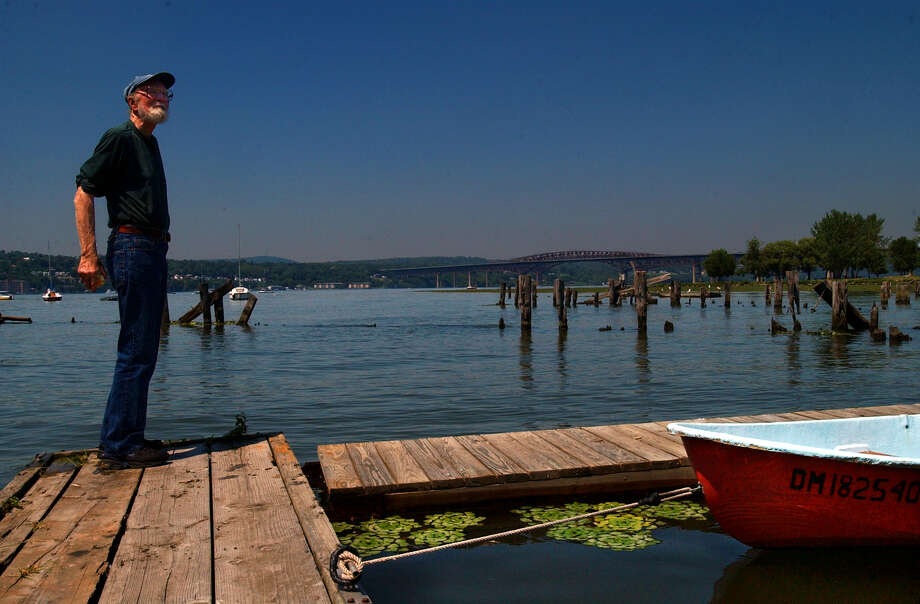 Times Union Staff photograph by Philip Kamrass -- Legendary folksinger Pete Seeger stands on a dock near old pilings for the former Newburgh Beacon ferry, with the Newburgh-Beacon bridge visible in the distance, on the Hudson River, during the Beacon Sloop Club Corn Festival in Beacon, NY Sunday August 11, 2002. Photo: PHILIP KAMRASS / ALBANY TIMES UNION