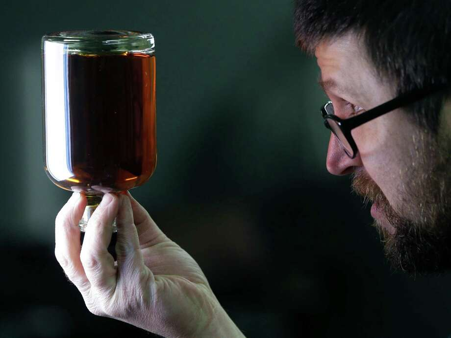 """Distilleryman Brian Messina inspects a bottle of baby bourbon on the bottling line at Tuthilltown Spirits on Wednesday, April 17, 2013, in Gardiner, N.Y. Some call it """"grain to glass,"""" the booze equivalent of the local-food slogan """"farm to table,"""" though in the case of the apple vodka made from Hudson Valley at Tuthilltown, it's more like """"tree to tumbler."""" Whatever the name, it's catching on. (AP Photo/Mike Groll) Photo: Mike Groll"""
