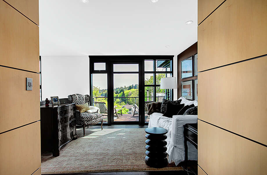 Room of 414 34th Ave. S., in Leschi. The 3,190-square-foot house, built in 1998, has three bedrooms, 2.25 bathrooms, a two-story living room with walls of windows, steel staircases and landing, decks, a patio, and views of Mount Rainier and Lake Washington on a 7,200-square-foot lot. It's listed for $1.8 million. Photo: HD Estates, Courtesy Kevin O'Doherty, Windermere Real Estate