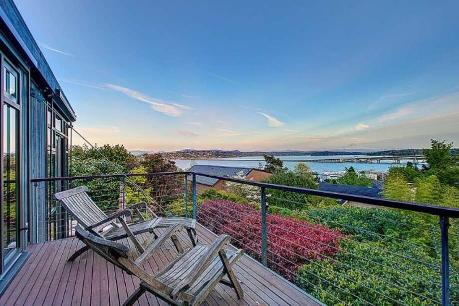 Deck of 414 34th Ave. S., in Leschi. The 3,190-square-foot house, built in 1998, has three bedrooms, 2.25 bathrooms, a two-story living room with walls of windows, steel staircases and landing, a patio, and views of Mount Rainier and Lake Washington on a 7,200-square-foot lot. It's listed for $1.8 million. Photo: HD Estates, Courtesy Kevin O'Doherty, Windermere Real Estate