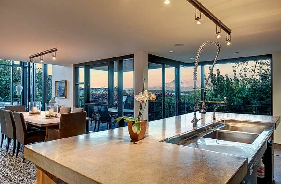 Kitchen and dining room of 414 34th Ave. S., in Leschi. The 3,190-square-foot house, built in 1998, has three bedrooms, 2.25 bathrooms, a two-story living room with walls of windows, steel staircases and landing, decks, a patio, and views of Mount Rainier and Lake Washington on a 7,200-square-foot lot. It's listed for $1.8 million. Photo: HD Estates, Courtesy Kevin O'Doherty, Windermere Real Estate