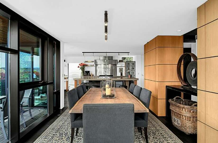 Dining room of 414 34th Ave. S., in Leschi. The 3,190-square-foot house, built in 1998, has three bedrooms, 2.25 bathrooms, a two-story living room with walls of windows, steel staircases and landing, decks, a patio, and views of Mount Rainier and Lake Washington on a 7,200-square-foot lot. It's listed for $1.8 million. Photo: HD Estates, Courtesy Kevin O'Doherty, Windermere Real Estate
