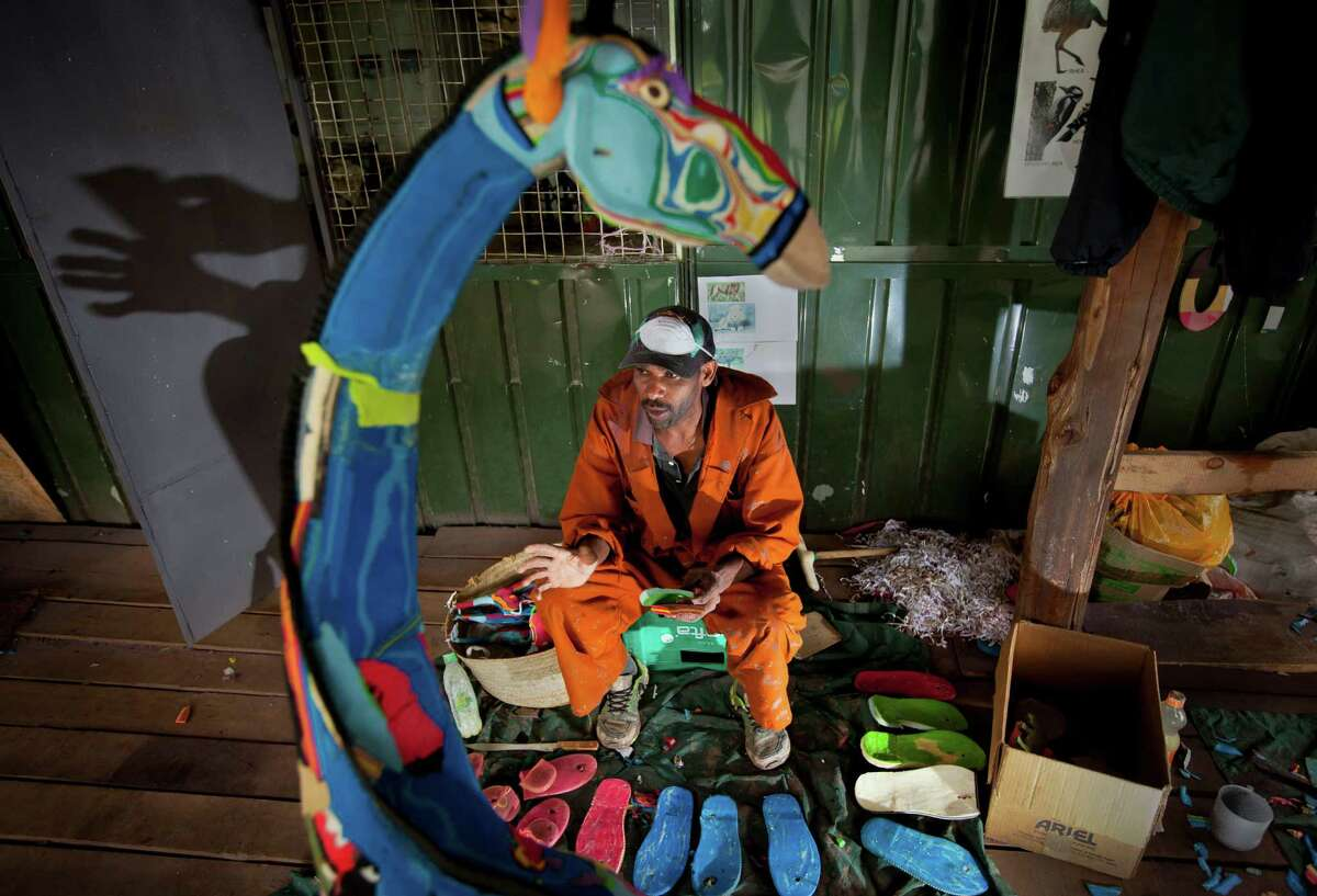 In this photo taken Monday, April 29, 2013, Jackson Mbatha, 40, sits with some of the discarded flip-flops he will carve up and glue together to make a large giraffe, at the Ocean Sole flip-flop recycling company in Nairobi, Kenya. The company is cleaning the East African country's beaches of used, washed-up flip-flops and the dirty pieces of rubber that were once cruising the Indian Ocean's currents are now being turned into colorful handmade giraffes, elephants and other toy animals.