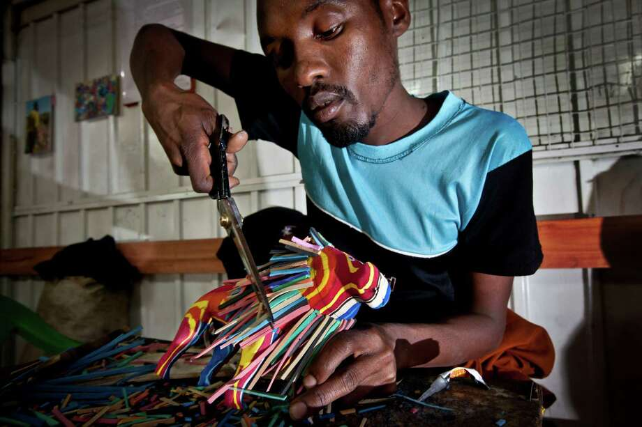 In this photo taken Monday, April 29, 2013, carver Daniel Lekalau, 26, uses scissors to trim the mane of a toy lion he is making from pieces of discarded flip-flops, at the Ocean Sole flip-flop recycling company in Nairobi, Kenya. The company is cleaning the East African country's beaches of used, washed-up flip-flops and the dirty pieces of rubber that were once cruising the Indian Ocean's currents are now being turned into colorful handmade giraffes, elephants and other toy animals. Photo: Ben Curtis, AP / AP