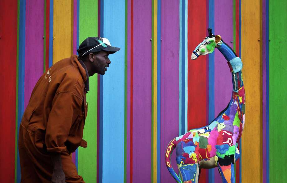 In this photo taken Monday, April 29, 2013, carver Jackson Mbatha, 40, poses next to a an unfinished large toy giraffe he is making from pieces of discarded flip-flops, in front of a painted workshop wall at the Ocean Sole flip-flop recycling company in Nairobi, Kenya. The company is cleaning the East African country's beaches of used, washed-up flip-flops and the dirty pieces of rubber that were once cruising the Indian Ocean's currents are now being turned into colorful handmade giraffes, elephants and other toy animals. Photo: Ben Curtis, AP / AP