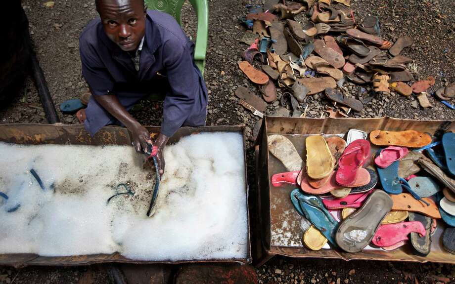 In this photo taken Monday, April 29, 2013, a worker washes and scrubs discarded flip-flops prior to them being sorted and carved into toy animals, at the Ocean Sole flip-flop recycling company in Nairobi, Kenya. The company is cleaning the East African country's beaches of used, washed-up flip-flops and the dirty pieces of rubber that were once cruising the Indian Ocean's currents are now being turned into colorful handmade giraffes, elephants and other toy animals. Photo: Ben Curtis, AP / AP