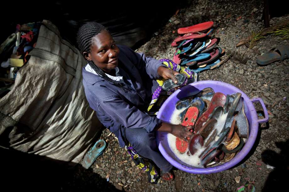 In this photo taken Monday, April 29, 2013, worker Jacqueline Achien washes discarded flip-flops in a bucket prior to them being sorted and carved into toy animals, at the Ocean Sole flip-flop recycling company in Nairobi, Kenya. The company is cleaning the East African country's beaches of used, washed-up flip-flops and the dirty pieces of rubber that were once cruising the Indian Ocean's currents are now being turned into colorful handmade giraffes, elephants and other toy animals. Photo: Ben Curtis, AP / AP