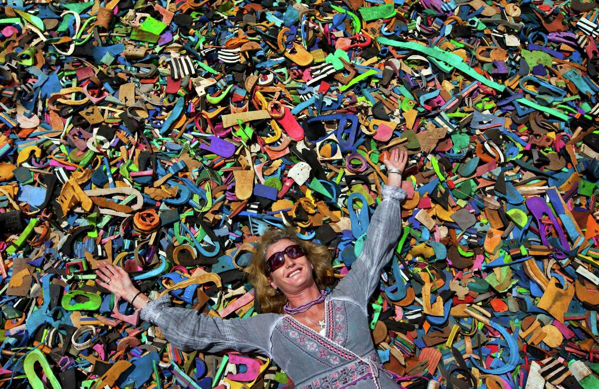 In this photo taken Monday, April 29, 2013, company owner and marine conservationist Julie Church poses for a photograph on a pile of pieces of discarded flip-flops used in a children's play area at the Ocean Sole flip-flop recycling company in Nairobi, Kenya. The company is cleaning the East African country's beaches of used, washed-up flip-flops and the dirty pieces of rubber that were once cruising the Indian Ocean's currents are now being turned into colorful handmade giraffes, elephants and other toy animals.