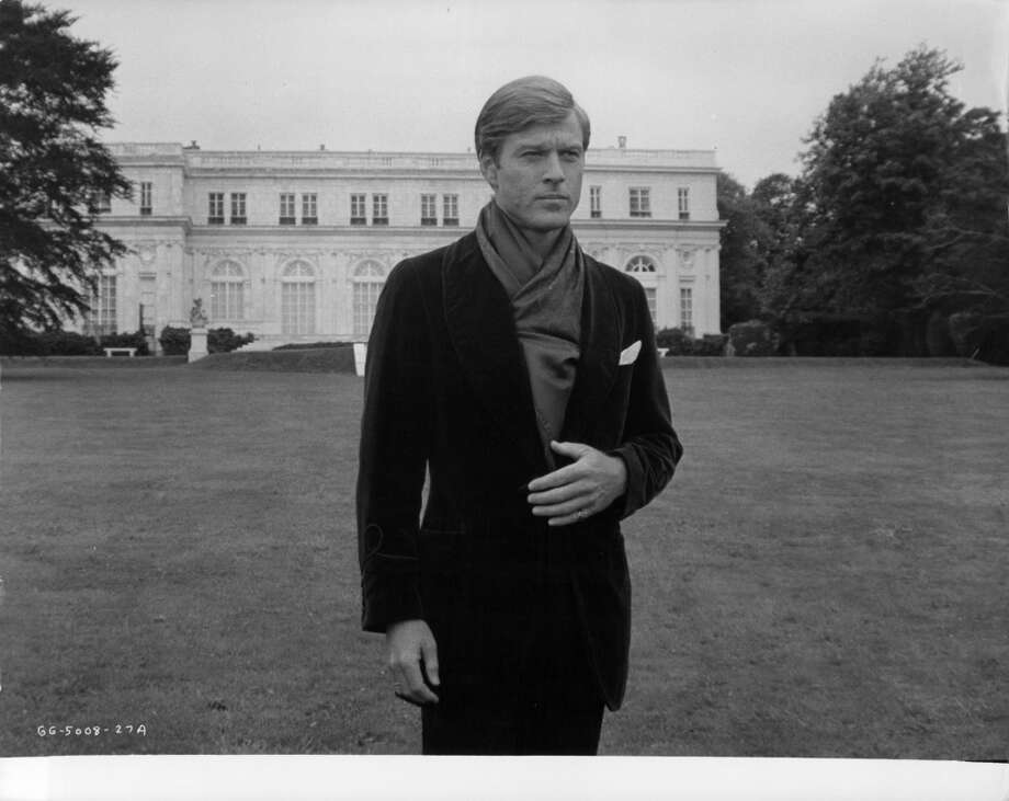 Robert Redford standing outside of mansion in a scene from the film 'The Great Gatsby', 1974.
