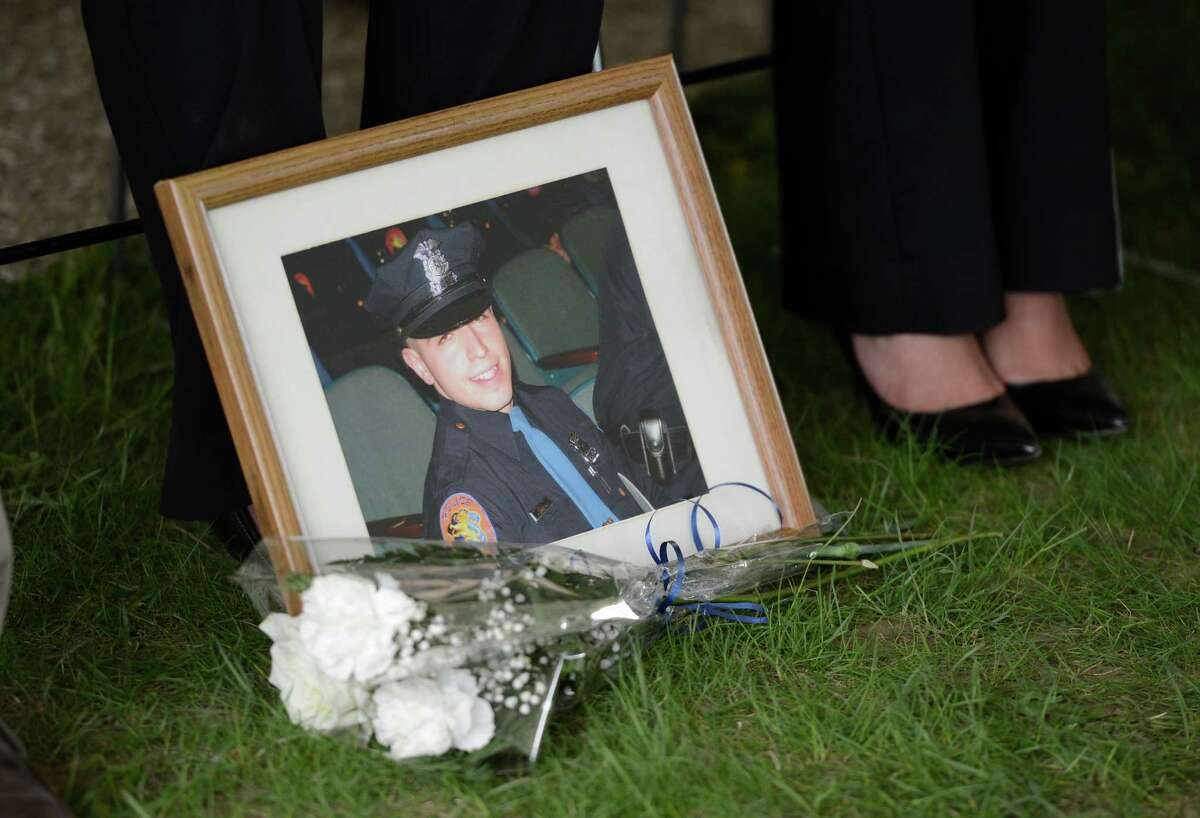 A photograph of deceased Nassau County officer Arthur Lopez sits at the feet of his sister Charo Ramos Wednesday May 8, 2013, during the State of New York Police Officers' Memorial Remembrance Ceremony in Albany, N.Y. (Skip Dickstein/Times Union)