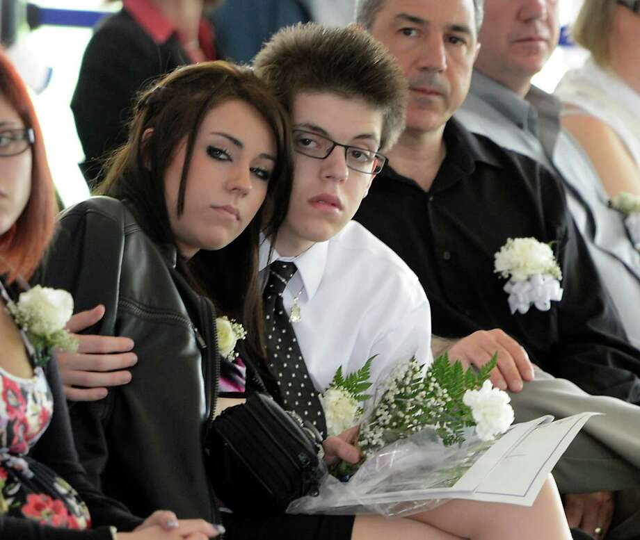 Daniel Oliveri, right, son of deceased Nassau County Police officer Joseph P. Olivieri Jr., comforts his girlfriend, Ali Mashburn, Wednesday May 8, 2013, during the State of New York Police Officers' Memorial Remembrance Ceremony in Albany, N.Y. Olivieri was struck and killed by an SUV while he investigated a motorcycle accident on the Long Island Expressway Oct. 18.  (Skip Dickstein/Times Union) Photo: SKIP DICKSTEIN / 00022315A