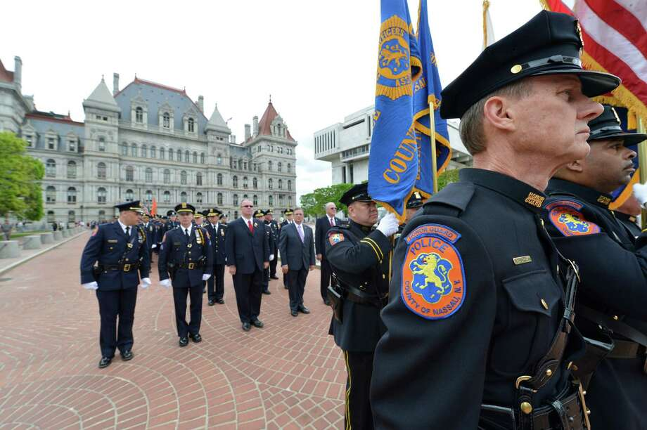 Members of the Nassau County Police and  honor guard enter the Empire Plaza Wednesday, May 8, 2013, for the State of New York Police Officers' Memorial Remembrance Ceremony in Albany, N.Y.   (Skip Dickstein/Times Union) Photo: SKIP DICKSTEIN / 00022315A