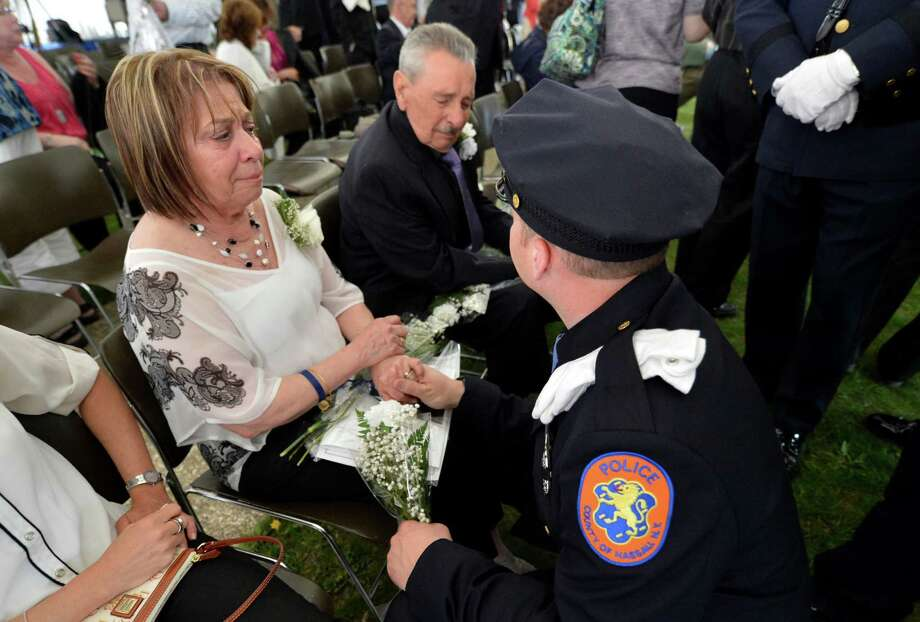Mirella Lopez is comforted by Nassau County Police officer Keith Blum on Wednesday, May 8, 2013, after the State of New York Police Officers' Memorial Remembrance Ceremony in Albany, N.Y. Lopez's son Nassau County Police officer Arthur Lopez was shot and killed during a traffic stop of a vehicle believed to be involved in a hit-and-run accident near the border of Queens County on Oct. 23, 2012.   (Skip Dickstein/Times Union) Photo: SKIP DICKSTEIN / 00022315A