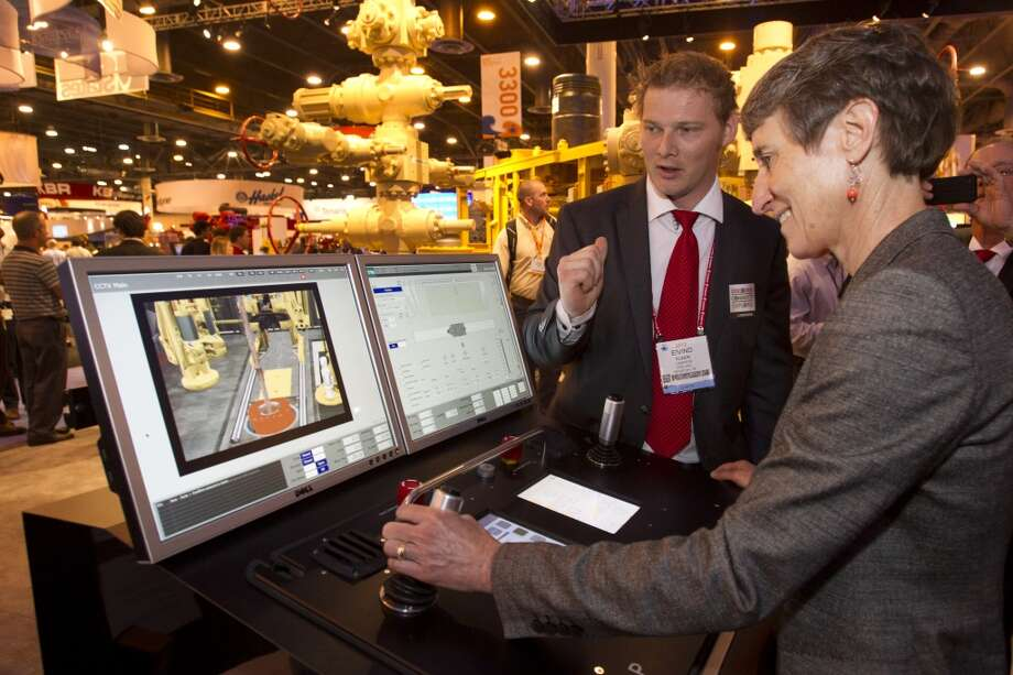 Eivind Sundel, left, helps Secretary of the Interior Sally Jewell, run a drilling simulator as she toured the exhibition floor during OTC2013 at Reliant Park Wednesday, May 8, 2013, in Houston. ( Brett Coomer / Houston Chronicle )