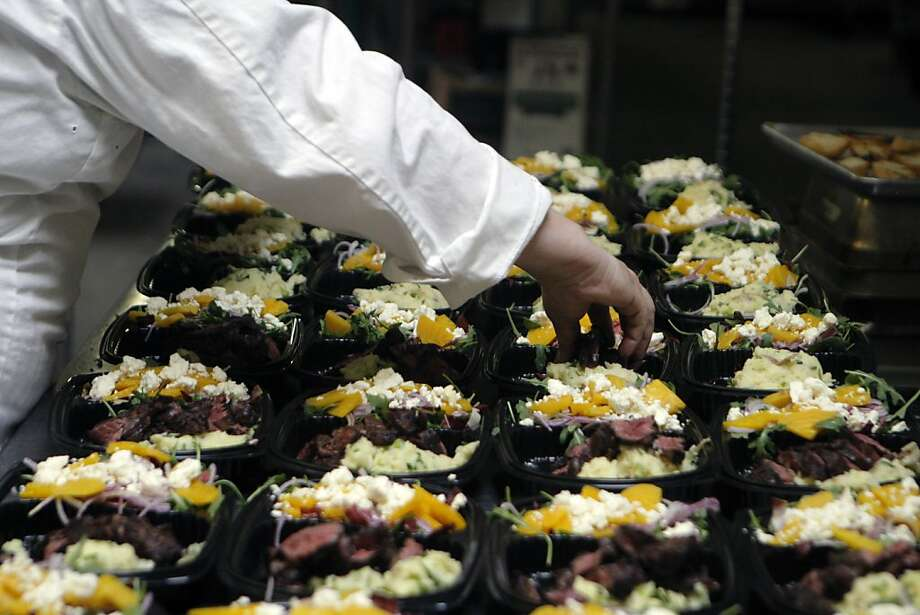 Steven Levine of Munchery prepares grilled hanger steak, smashed potatoes and beet-feta salad at the meal delivery service's San Francisco kitchen. Photo: Jessica Olthof, The Chronicle