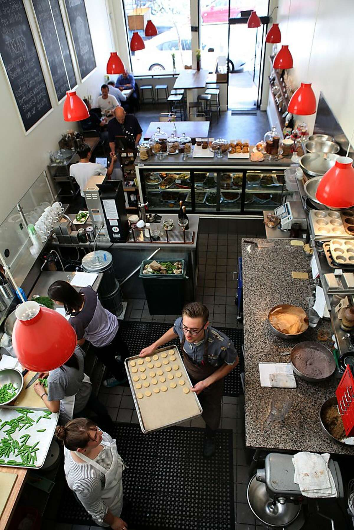 Workers prepare food at Square Meals, which features ribollita soup made with white beans, squash and kale, and a salad of sugar snap peas, radishes, pea tendrils and yogurt cheese.