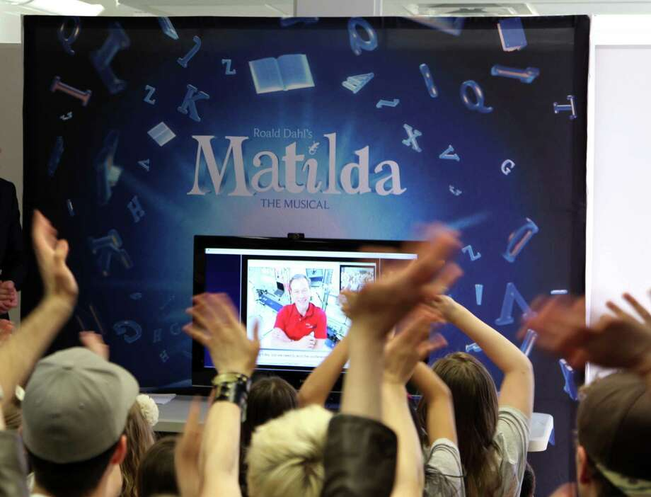 "This May 7, 2013 photo shows the cast of the Tony Award-nominated ""Matilda"" waving to Tim Marshburn, one of six astronauts aboard the International Space Station, via a satellite hook-up provided by NASA, at a gathering in New York. Cast members, including many children, packed a small room near Times Square on Tuesday to ask questions about life in space.  (AP Photo/Mark Kennedy) Photo: Mark Kennedy"