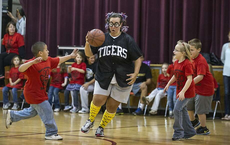 The faculty wins again, as usual: Instructor Jackie LeMonds dribbles around lilliputians during the annual teachers-vs.-first-graders/kindergarteners 