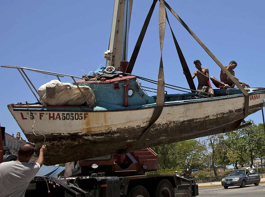 And it seemed so seaworthy: Two fishermen assist as a crane lowers their boat, the Ivana, in Old Havana, Cuba. The young men were rescued by 