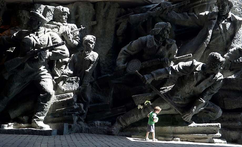 An admirer of a World War II monument in Kiev inspects a hand that's bigger than his head on Victory Day. Photo: Sergei Supinsky, AFP/Getty Images