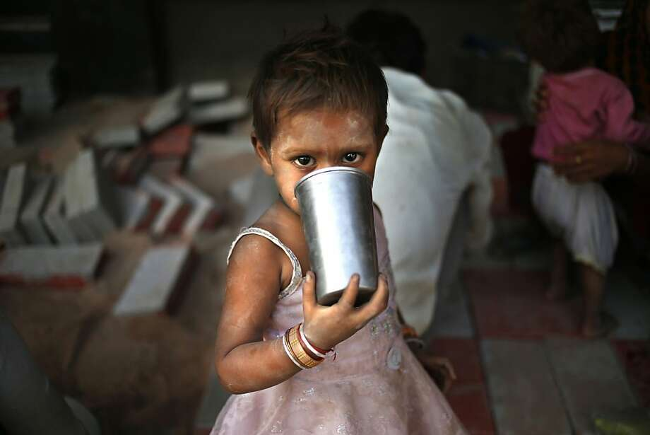 """Sippy cup:Every day is """"Take Your Daughter to Work"""" day for parents working on a crew constructing a pavement   in New Delhi. Photo: Saurabh Das, Associated Press"""