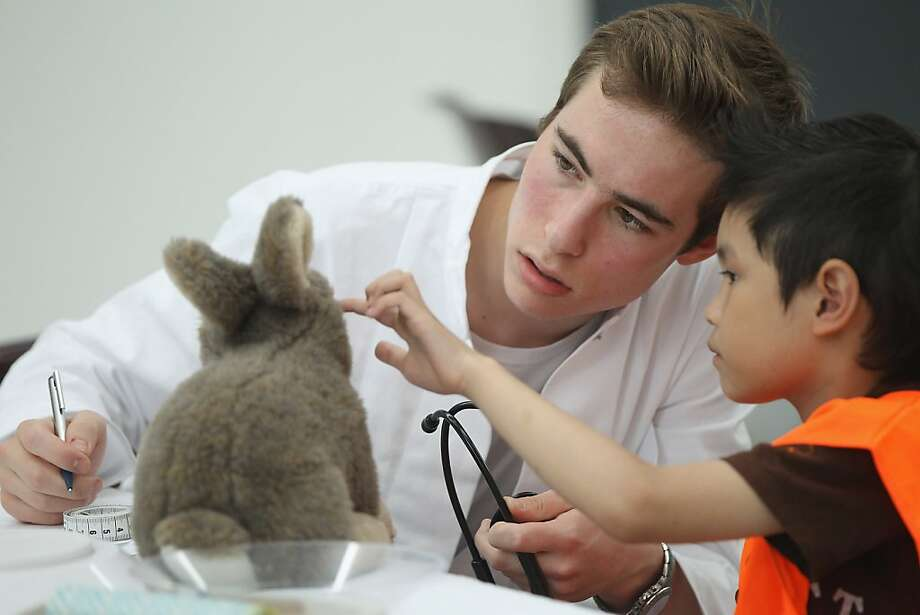 Somebody poked him in the eye - like this: A boy tells a medical student what's ailing his stuffed rabbit at the 