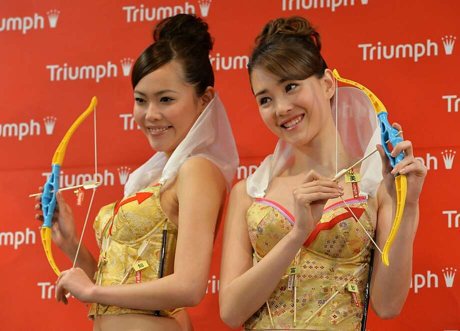 "Cupid is as Cupid does:Triumph International models show off the ""Branomics Bra,"" an undergarment inspired by Japanese Prime Minister Shinzo Abe's ""Abenomics"" economic policy, in Tokyo. The toy arrows represent Abe's ""three arrows"" stimulus package. Photo: Yoshikazu Tsuno, AFP/Getty Images"