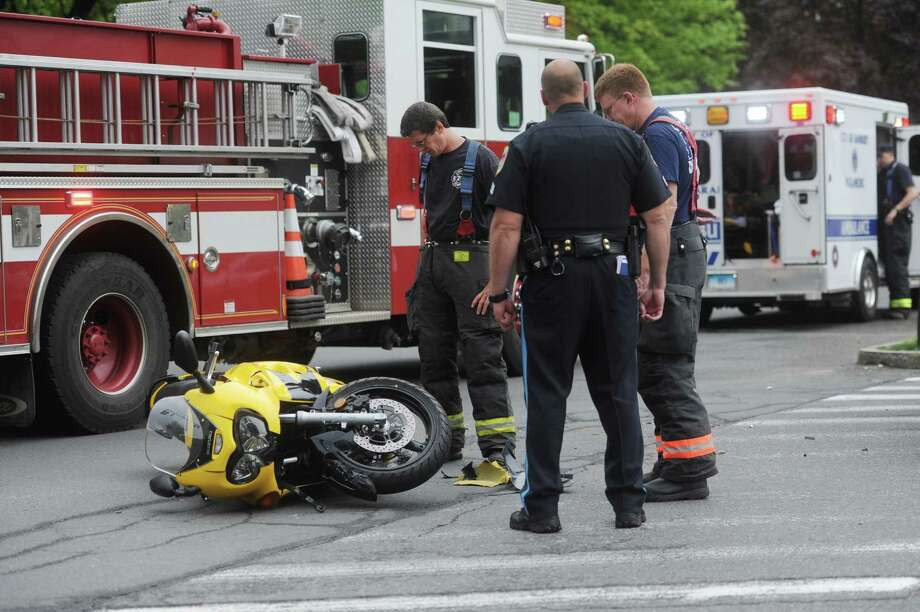 Police and fire crews investigate the scene of a hit-and-run accident at the intersection of Deer Hill Avenue and West Wooster Street in Danbury, Conn. on Wednesday, May 8, 2013.  A man riding a street bike was injured in the crash. Photo: Tyler Sizemore / The News-Times