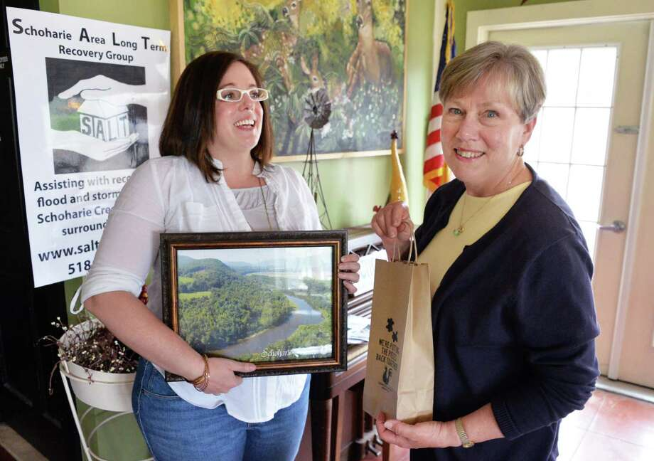 Jessica Kirby, left, of the Schoharie Valley Association and Sarah Goodrich, executive director of Schoharie Area Long Term (SALT) announce a new fund raiser for the flood ravaged county during a news conference in Schoharie, NY Wednesday May 8, 2013. Participants start by donating $5 or more to SALT; in return they receive a puzzle collection bag and travel throughout the valley visiting local shops and businesses to collect all the puzzle pieces.  (John Carl D'Annibale / Times Union) Photo: John Carl D'Annibale / 00022317A