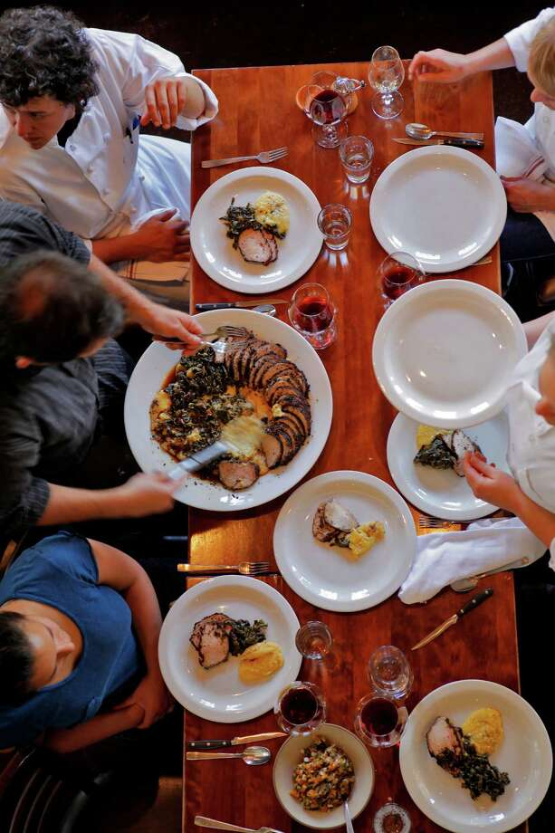 Nopa restaurant owner Laurence Jossel, left, serves the main dish which was roasted pork loin to the staff and  owners of Tomatero Farms and owners of the Mount Eden Vineyards at the close the circle lunch, Monday June 29, 2010, in San Francisco, Calif. The close the circle lunch is an idea to give the cooks and servers a better understanding of how the food is produced. Photo: Lacy Atkins / The Chronicle / SFC
