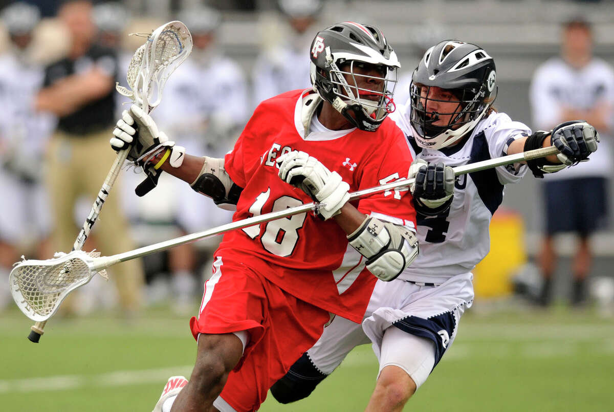 Fairfield Prep's Austin Sims runs down the field while under pressure from Wilton's Henry Lee during their game at Wilton High School on Wednesday, May 8, 2013. Fairfield Prep won, 16-9.