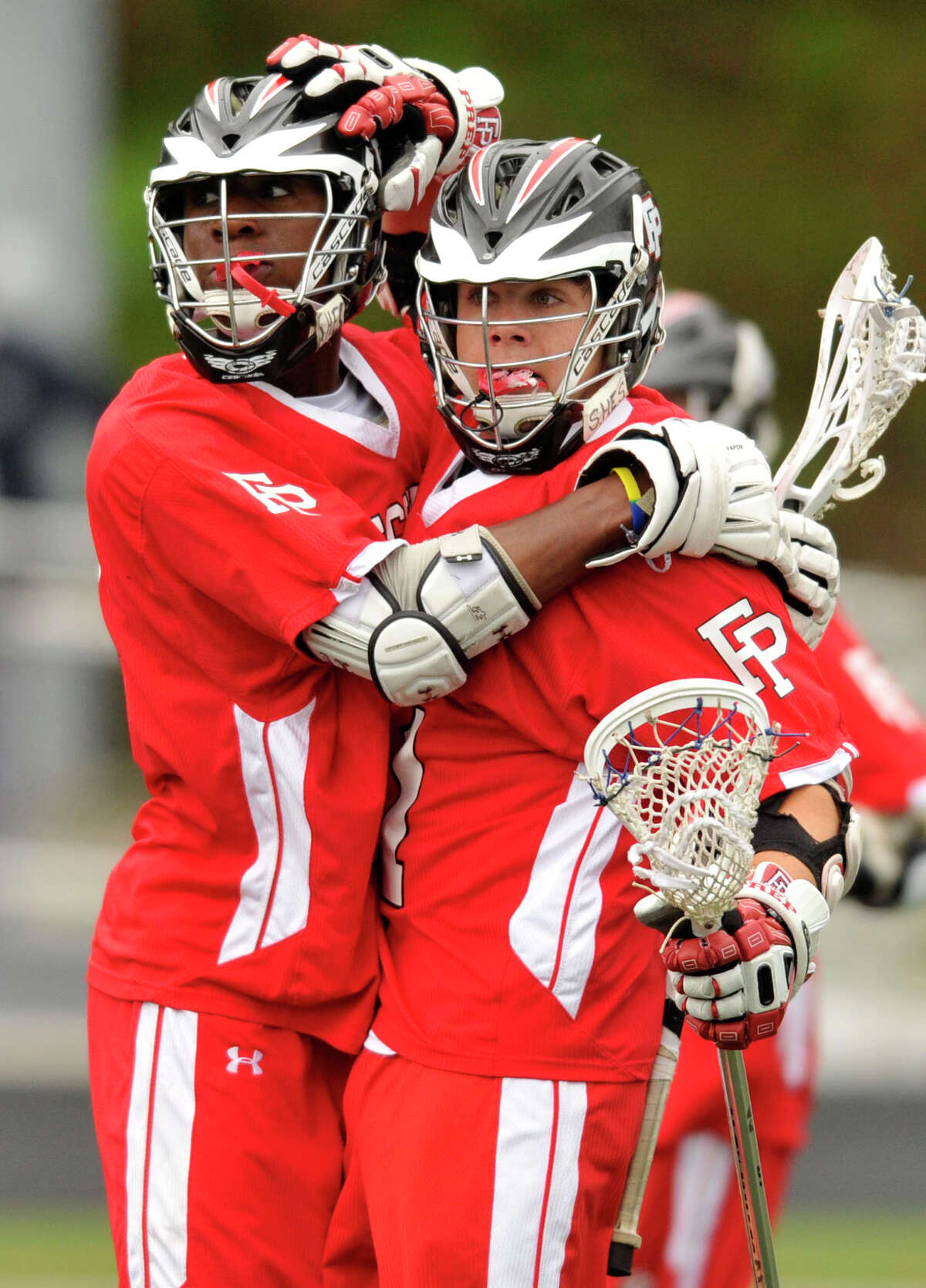Fairfield Prep's Kevin Brown, right, congratulates his fellow teammate Austin Sims after Sims scored in their game at Wilton High School on Wednesday, May 8, 2013. Fairfield Prep won, 16-9.
