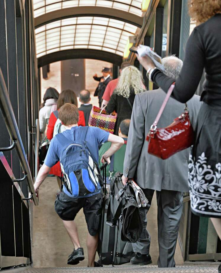 Passengers carrying luggage down the stairs the Amtrak station in Rensselaer, NY Wednesday May 8, 2013. Escalators at the station have been out of service for six weeks, forcing riders to haul their bags up and down the stairs. (John Carl D'Annibale / Times Union) Photo: John Carl D'Annibale /  00022333A