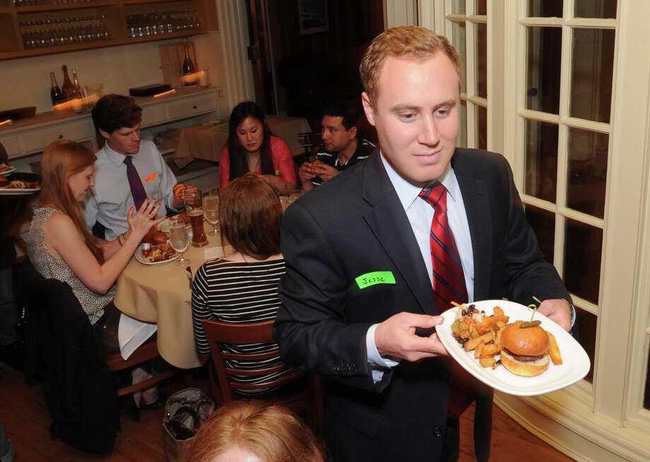 Jesse Leeds-Grant of Dishcrawl, a business that takes participants on restaurant tours, serves food during the event at the Ginger Man restaurant in Greenwich, Wednesday, May 8, 2013. Photo: Bob Luckey / Greenwich Time
