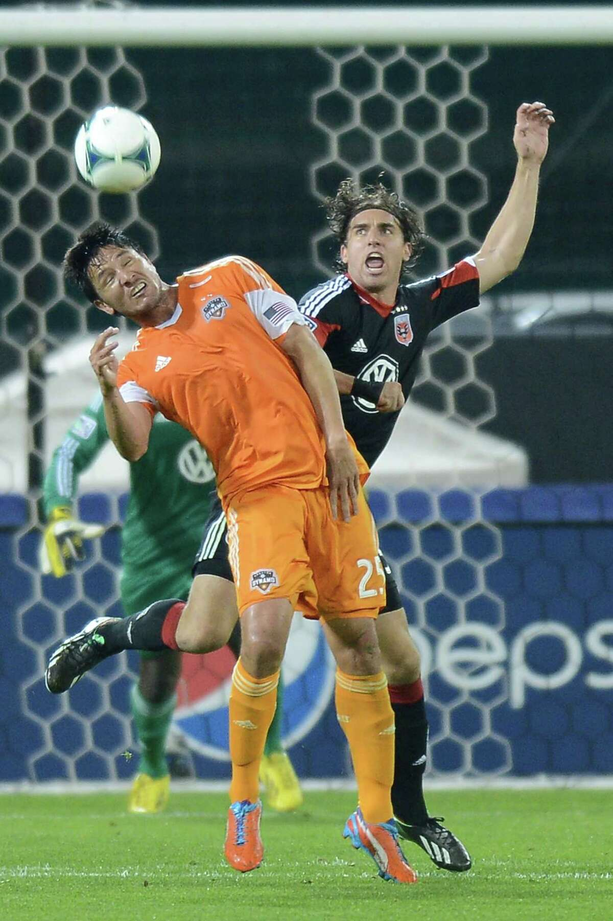 Houston Dynamo forward Brian Ching (25) and D.C. United defender Dejan Jakovic (5) battle for a head ball in the second half at RFK Stadium in Washington, D.C., Wednesday, May 8, 2013. Dynamo blanked United, 4-0. (Chuck Myers/MCT)