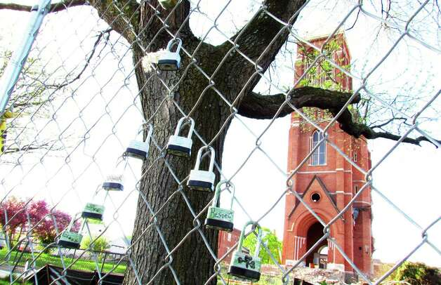 Locks on a fence are shown in front of the remains of the bell tower on St. Patrick's Church in Watervliet  on Wednesday, May 8, 2013. (Courtesy Ron Schubin)