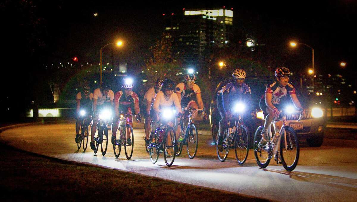 A group of cyclists enjoy a night road ride along MacGregor Drive in Houston. The city's safe passing ordinance requires motorists to give bikers ample room.