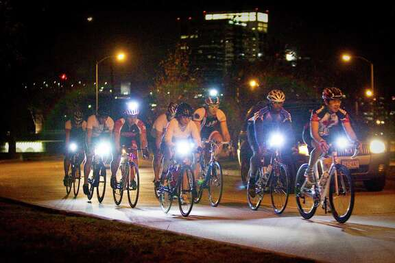 A group of cyclists enjoy a night road ride along MacGregor Drive in Houston. The city's new ordinance requires motorists to give bikers ample room.