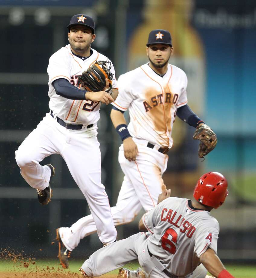 Astros second baseman Jose Altuve (27) completes the double play.