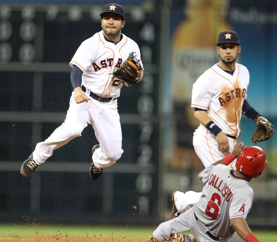 Astros second baseman Jose Altuve (27) completes a double play.