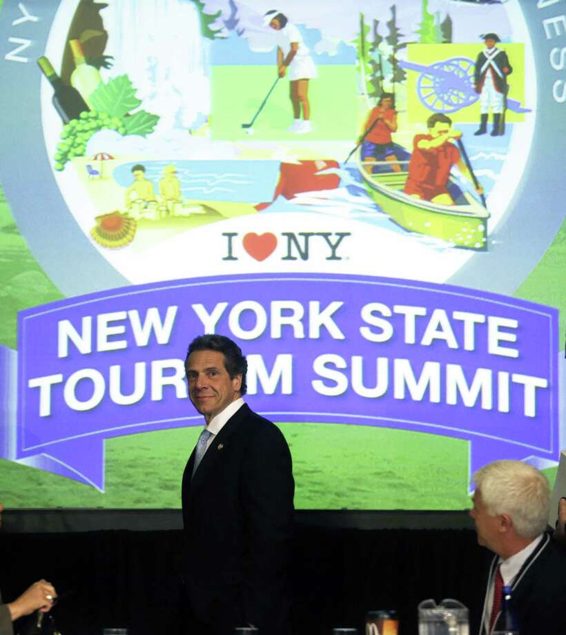 New York Gov. Andrew Cuomo arrives for the New York State Tourism Summit on Wednesday, May 8, 2013, in Albany, N.Y.  The governor is trying to map out a better way to showcase New York state's seasonal attractions and boost businesses. The focus will range from summer attractions such as Niagara Falls, the Erie Canal and Adirondacks to the rebuilding of boardwalks and beaches on Long Island hit hard by Superstorm Sandy last fall. (AP Photo/Mike Groll) Photo: Mike Groll
