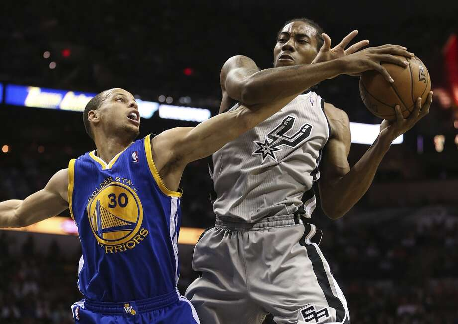 San Antonio Spurs' Kawhi Leonard gets a rebound under pressure from Golden State Warriors' Stephen Curry during the first half of Game 2 in the NBA Western Conference semifinals at the AT&T Center, Wednesday, May 8, 2013. Curry was called for a foul.