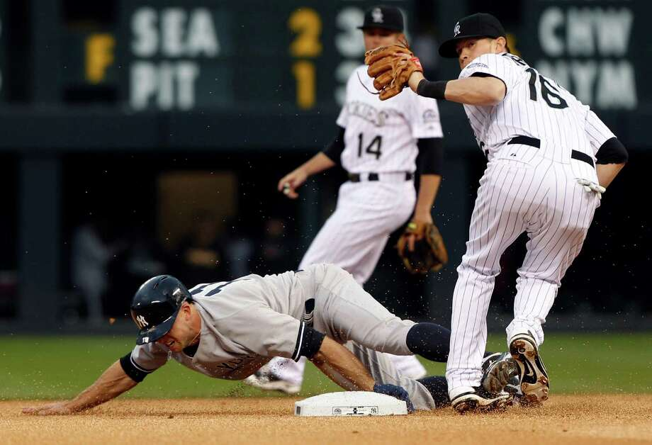 New York Yankees' Brett Gardner, front left, slides safely into second base as Colorado Rockies shortstop Reid Brignac, front right, fields the throw and second baseman Josh Rutledge backs up the play in the first inning of a baseball game in Denver on Wednesday, May 8, 2013. (AP Photo/David Zalubowski) Photo: David Zalubowski
