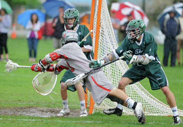 Niskayuna's Lucas Maloney reaches around the net and tries to score during a lacrosse game against S