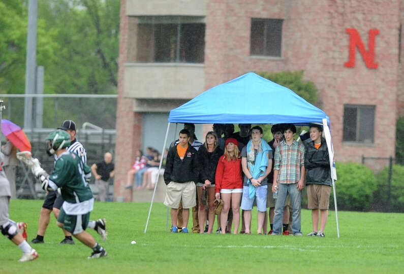 Students stay dry under a canopy during a rainy lacrosse game between Niskayuna's and Shenendehowa o
