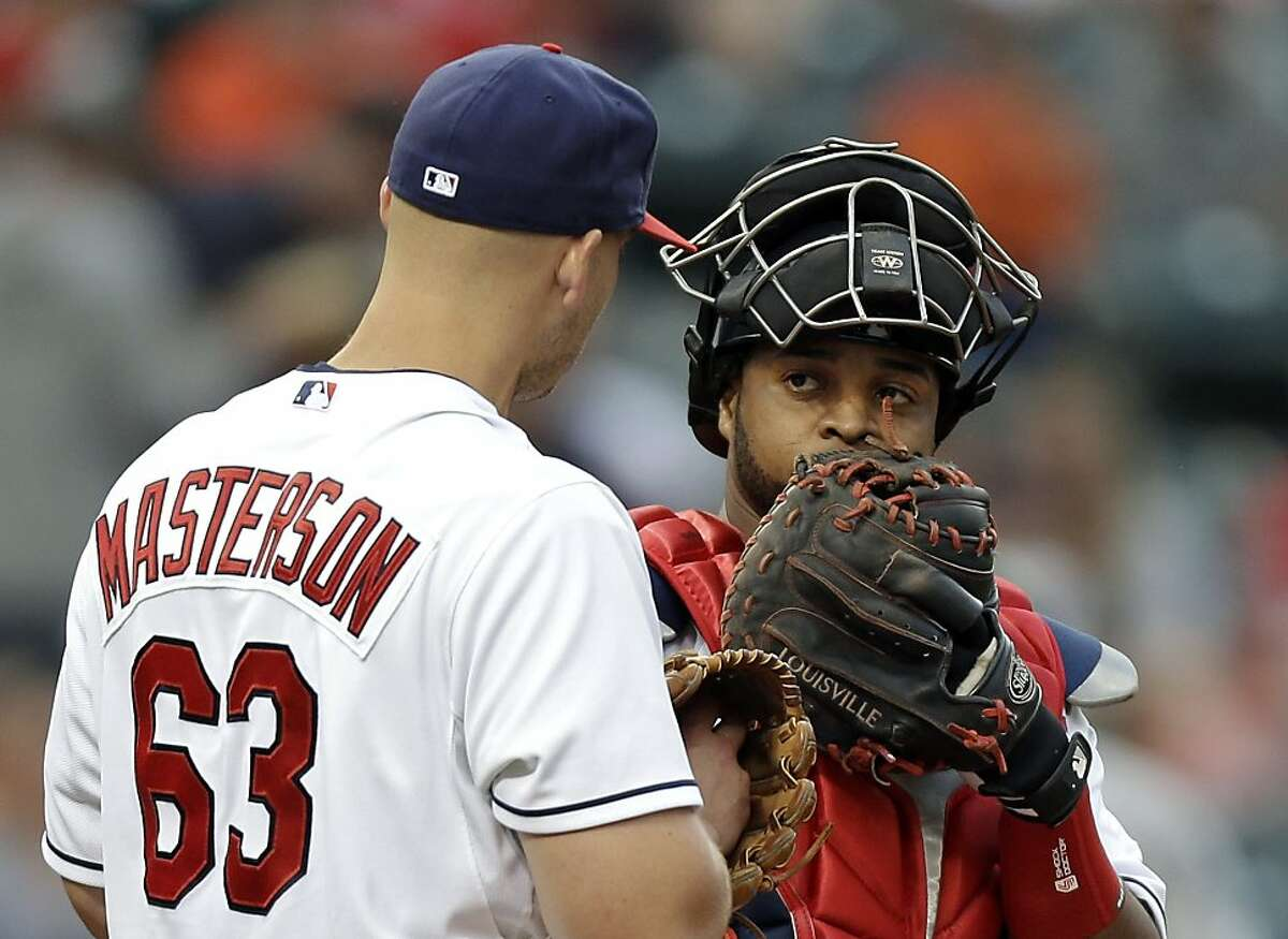 Cleveland Indians catcher Carlos Santana talks to starting pitcher Justin Masterson in the fourth inning of a baseball game against the Oakland Athletics on Wednesday, May 8, 2013, in Cleveland. (AP Photo/Mark Duncan)