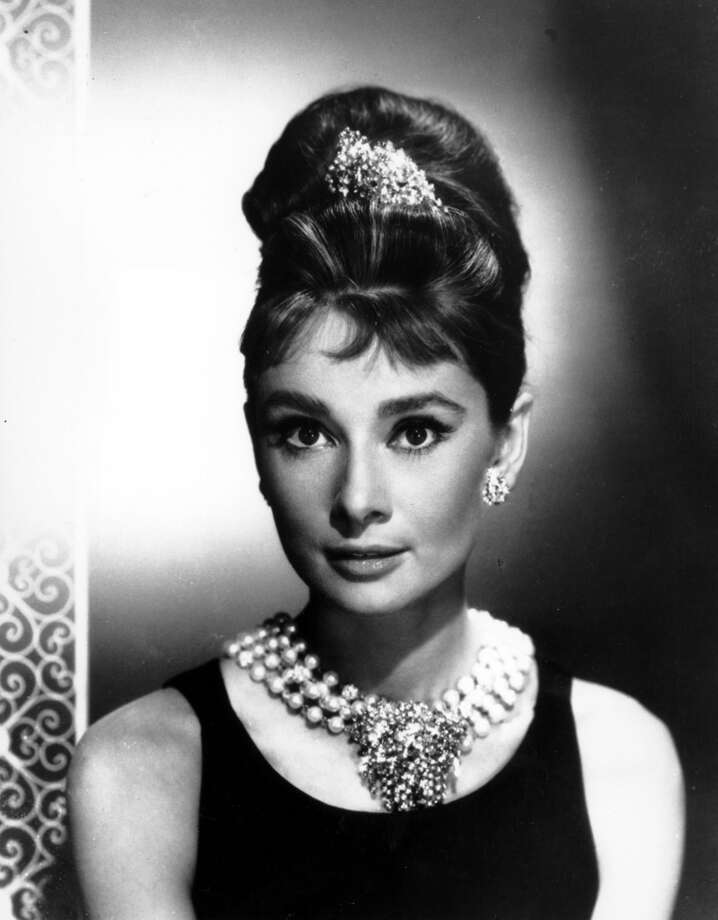 "Audrey Hepburn, style icon for the ages, twists her long hair into an updo for her leading role in ""Breakfast at Tiffany's."""