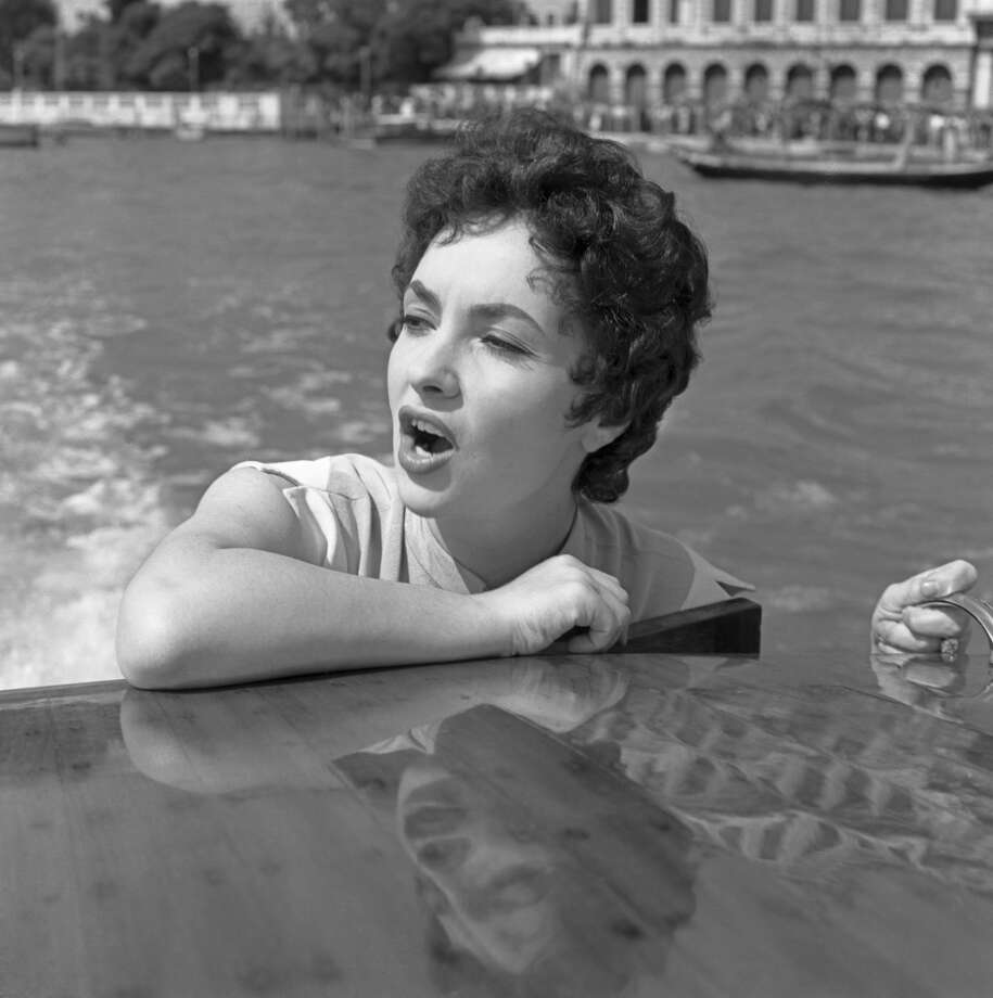 Italian actress Gina Lollobrigida portrayed in a close-up, leaning against the water taxi roof, singing, in the Canal Grande, Venice 1954. (Photo by Archivio Cameraphoto Epoche/Getty Images)